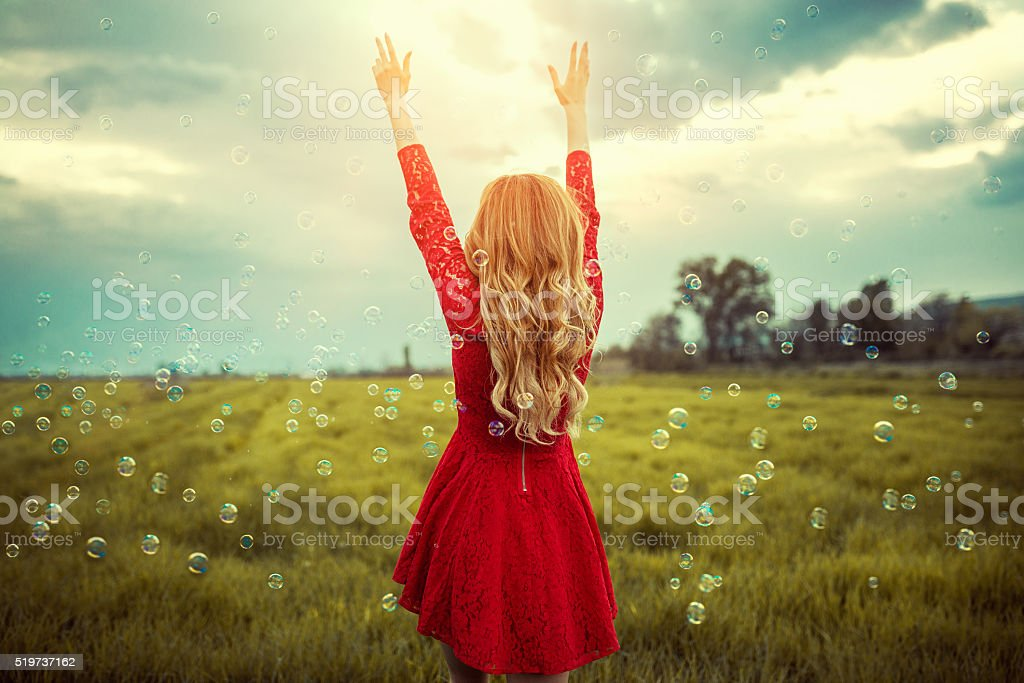 Blonde Girl Enjoying Nature with Spread Arms Surrounded with Bubbles stock photo