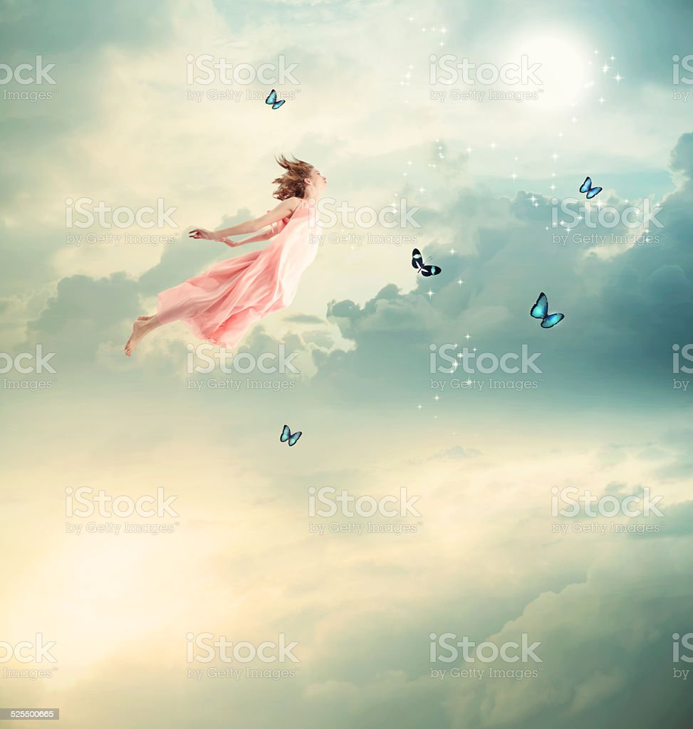 Blonde Girl Flying with Butterflies stock photo