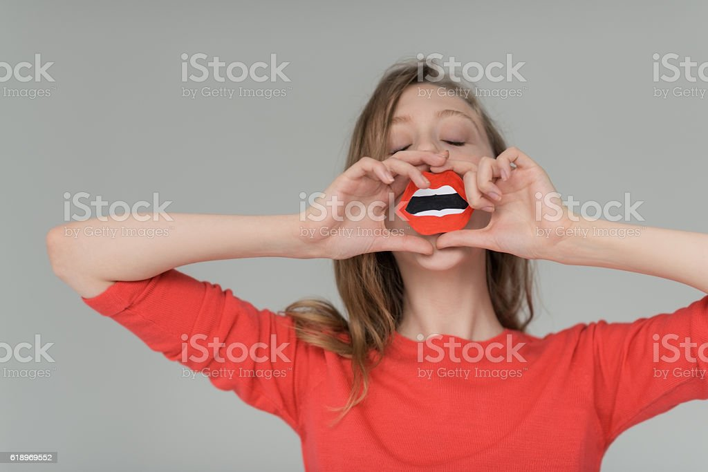 Blonde girl holding paper mouth sign stock photo