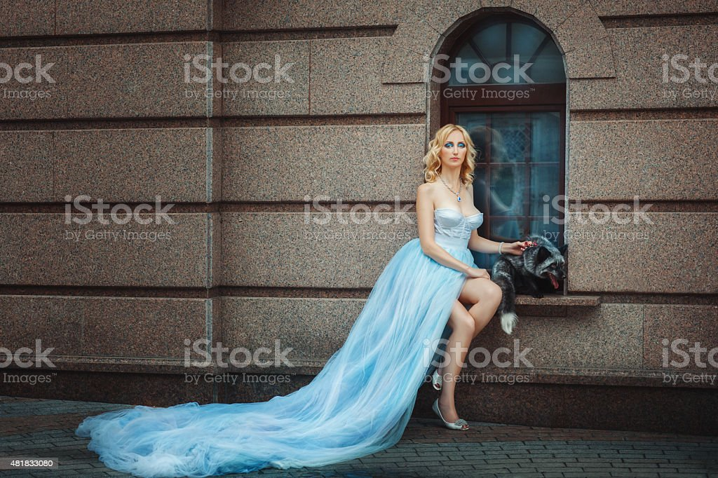 Blonde girl in a blue long dress. stock photo