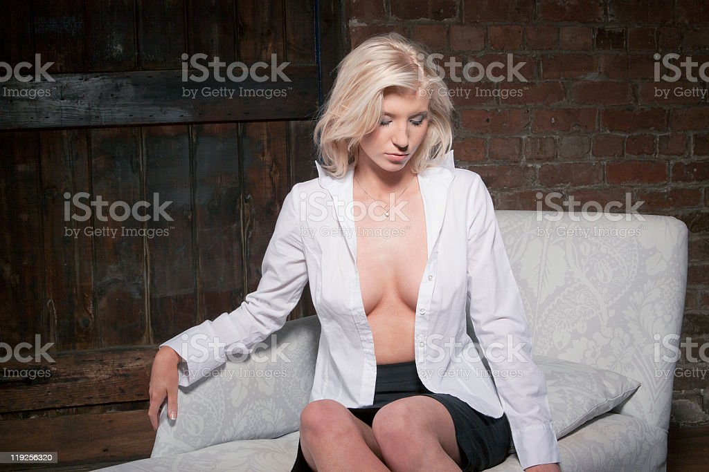 Blonde girl in a white shirt revealing her breasts. stock photo