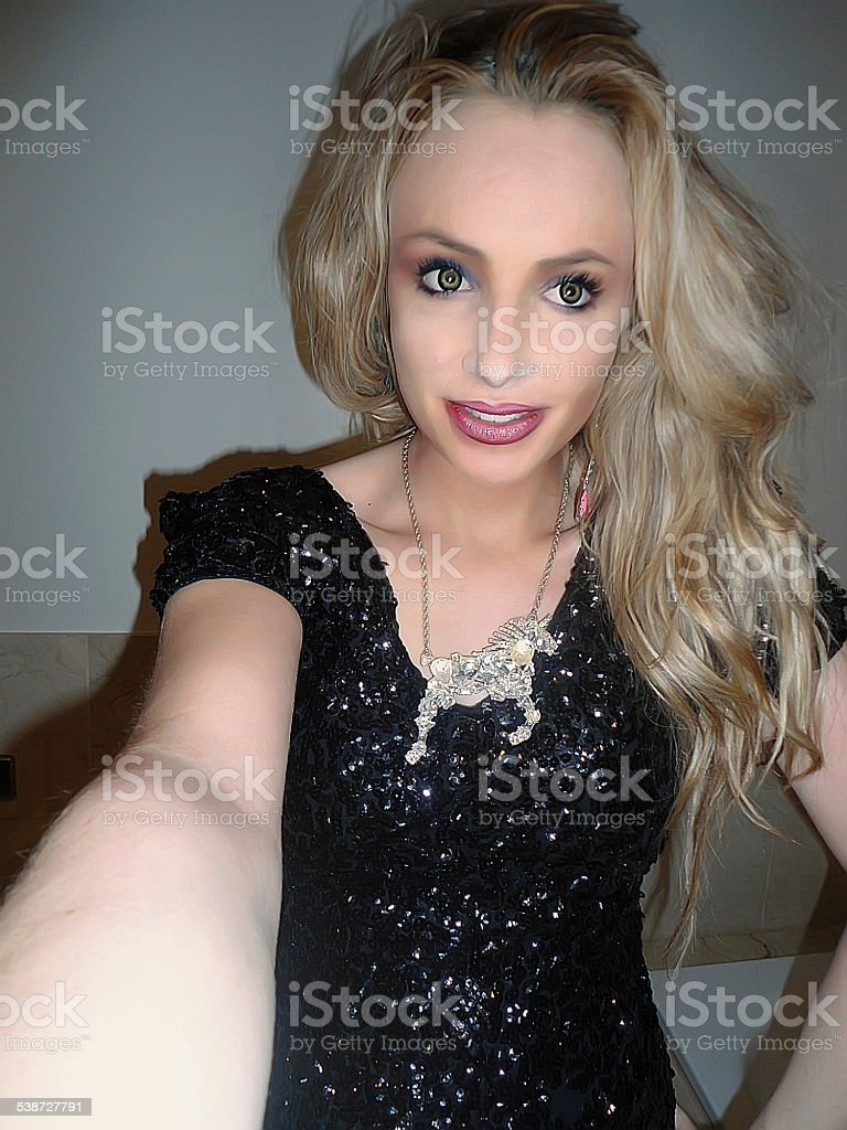 Blonde girl in sparkly dress and unicorn necklace selfie stock photo