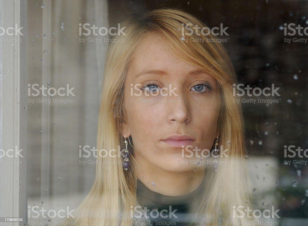 Blonde girl looking through  window royalty-free stock photo