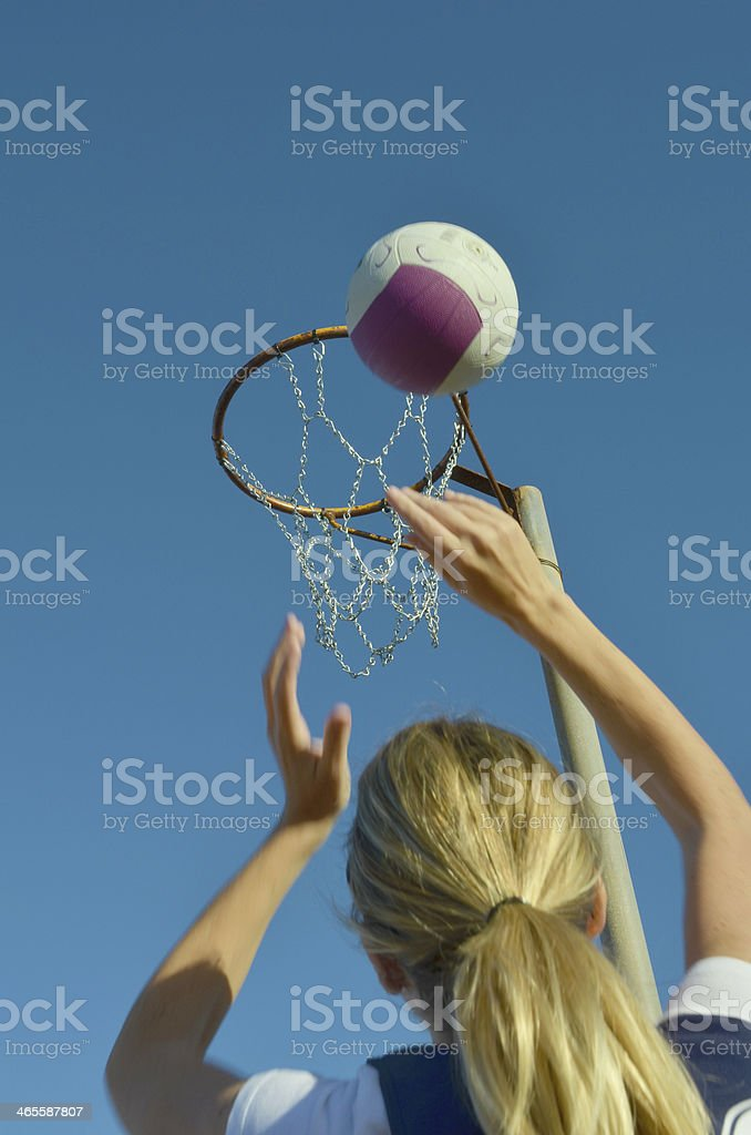 Blonde girl playing and shooting a netball goal stock photo