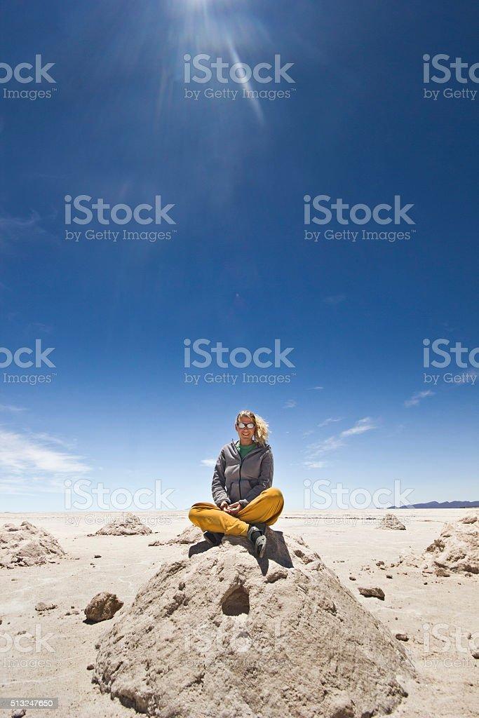 blonde girl sitting on salt heap at Salar Uyuni, Bolivia stock photo