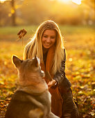 Blonde girl walking in the park with her dog.