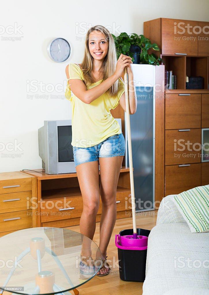 Blonde girl washing parquet floor stock photo