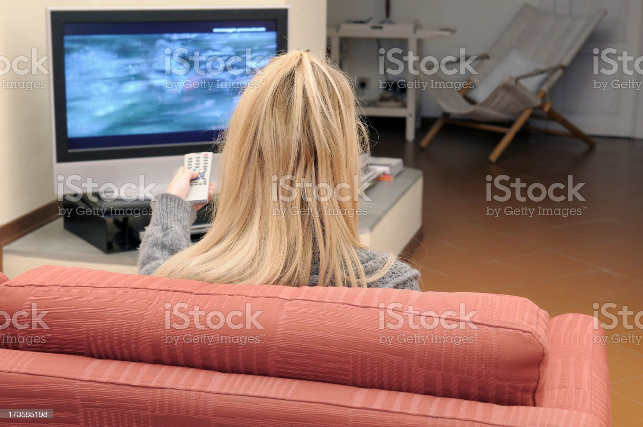 Blonde Girl Watching Television on Sofa royalty-free stock photo