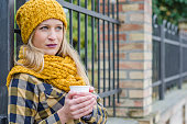 Blonde girl with a hat and a scarf standing outside