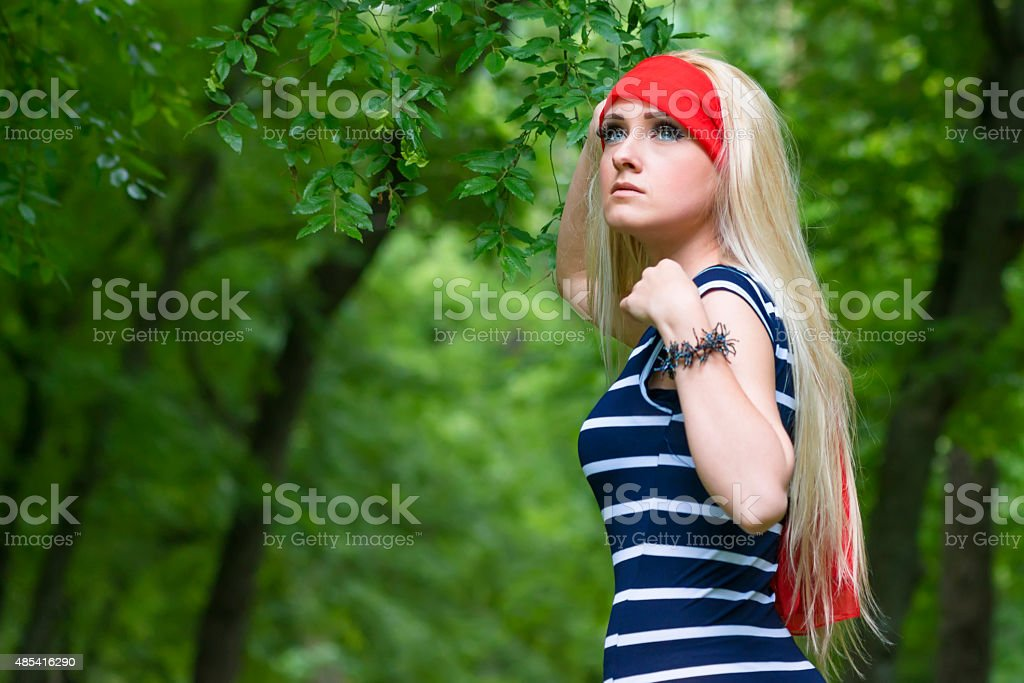 blonde girl with red scarf and striped dress stock photo