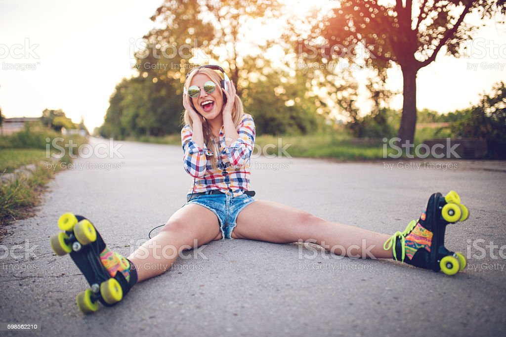 Blonde girl with roller skates stock photo