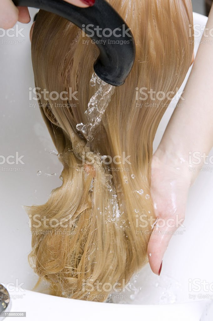 Blonde hair being washed on a white sink with black faucet stock photo