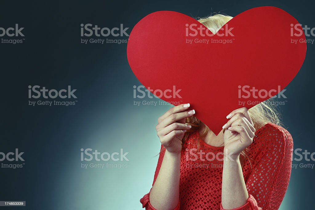 Blonde haired woman hiding a heat shape royalty-free stock photo