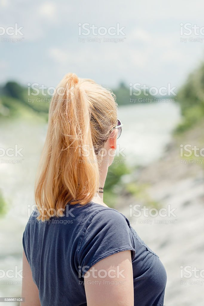 Blonde haired woman looking down the river stock photo