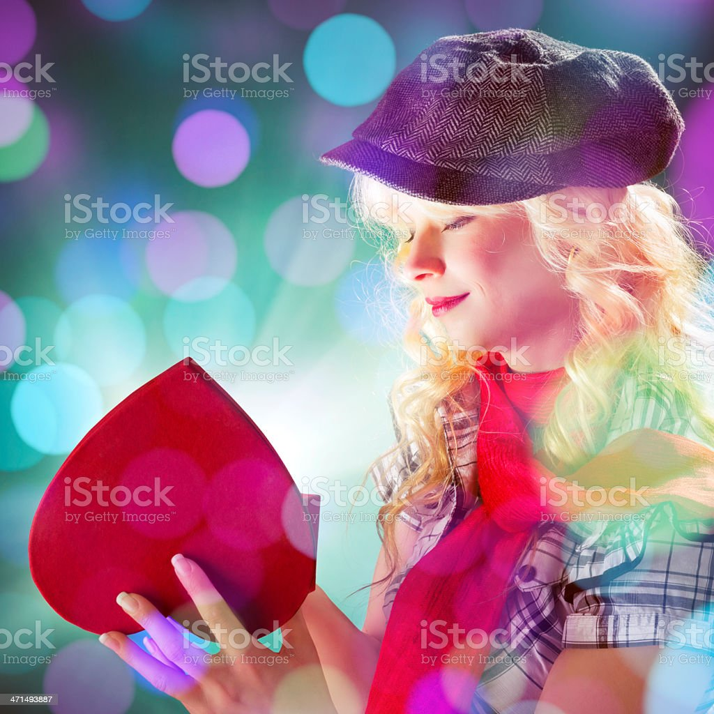 Blonde haired woman opening a heart shaped box gift royalty-free stock photo