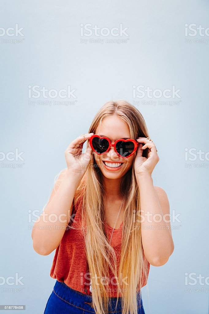 Blonde happy teenage girl with heart sunglasses stock photo