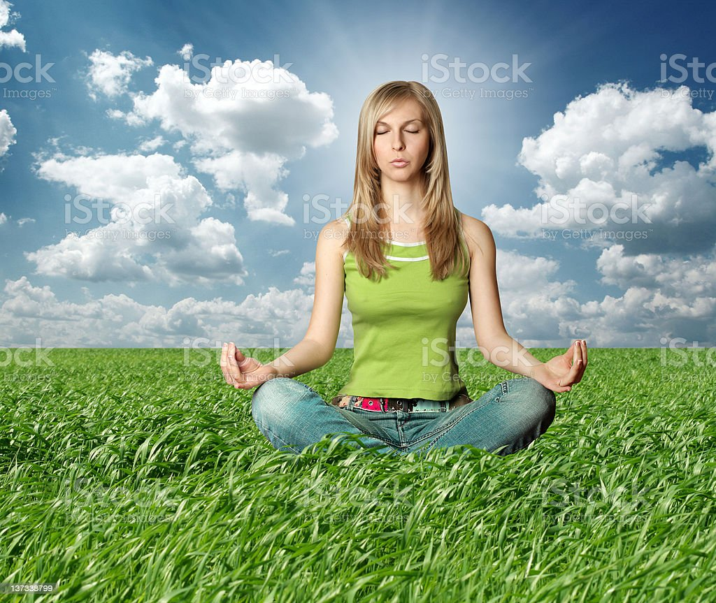 Blonde in lotus pose and green grass royalty-free stock photo