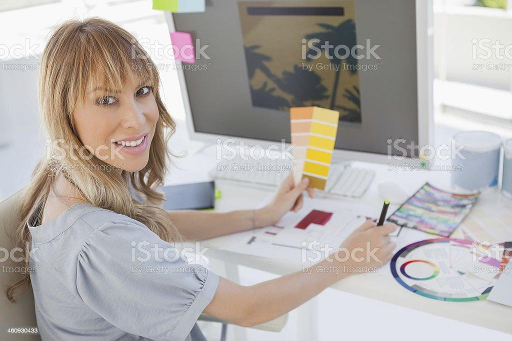 Blonde interior designer working at her desk royalty-free stock photo