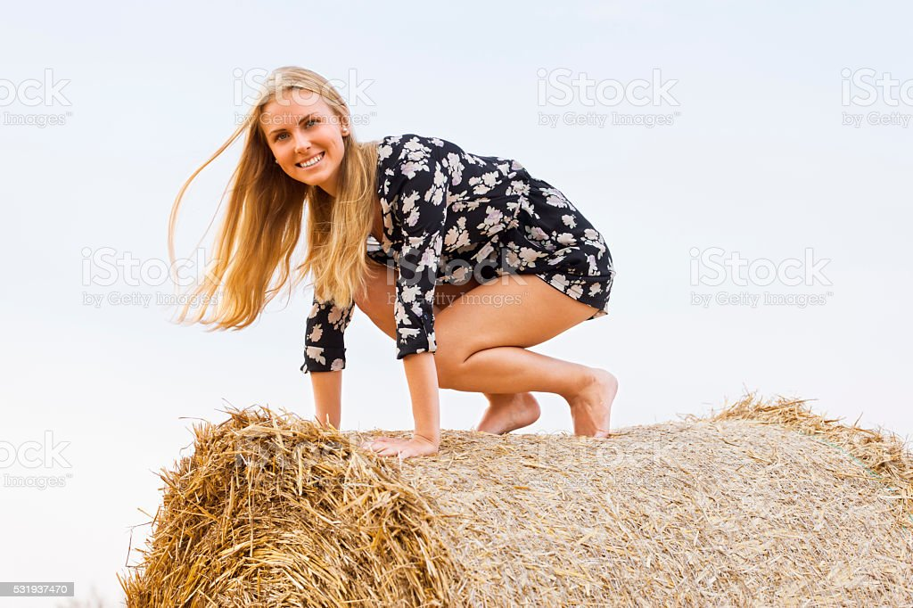 Blonde jumps from straw bale down stock photo