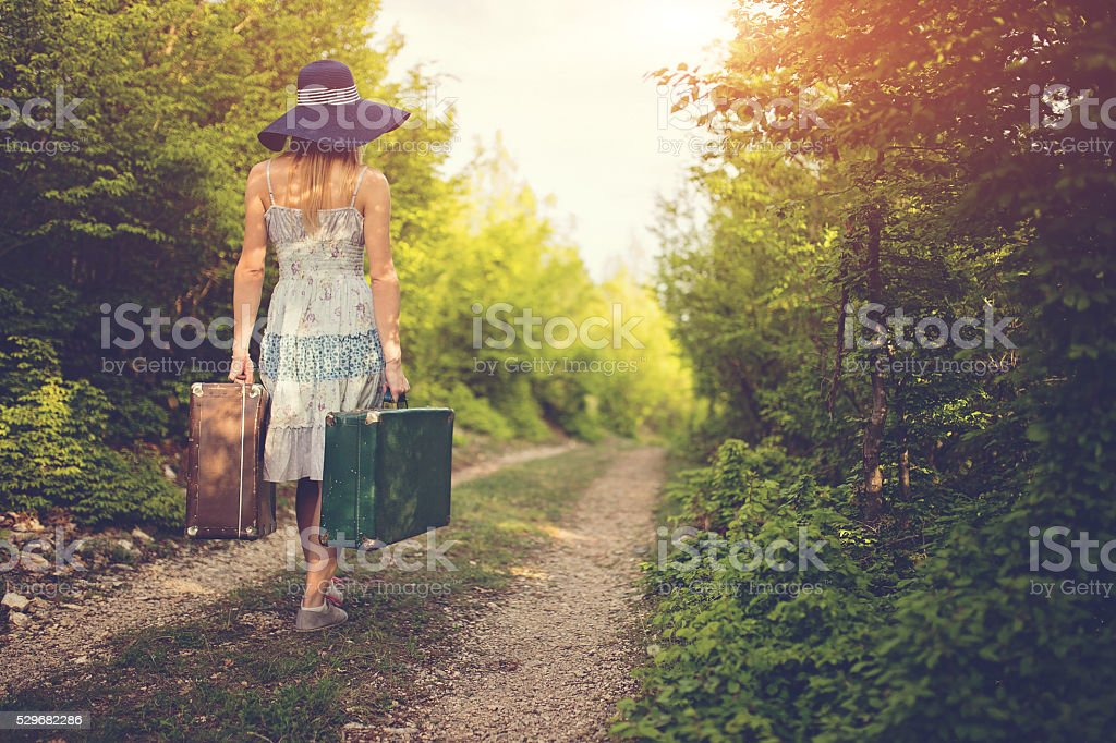Blonde lady with suitcases stock photo