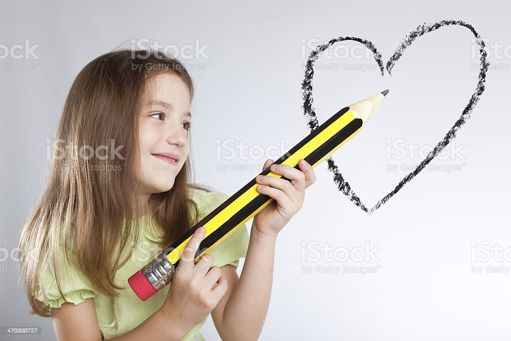 Blonde little girl drawing with giant pencil heart royalty-free stock photo