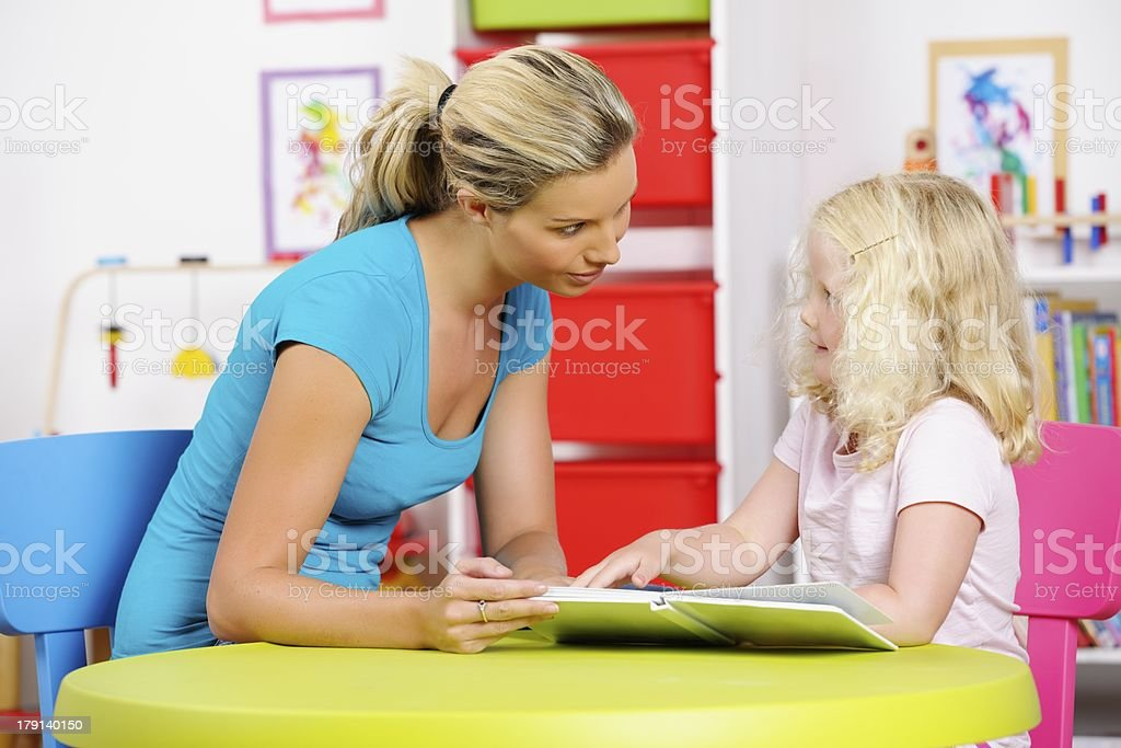 Blonde Little Girl Highlighting Something To Her Carer At Nursery royalty-free stock photo