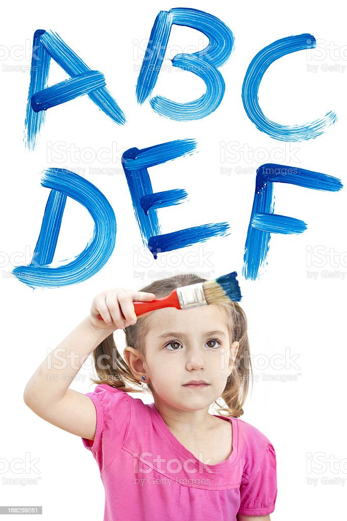 Blonde little girl painting with blue ABC on window stock photo