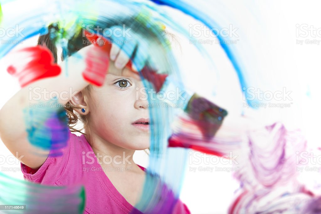 Blonde little girl painting with colours on window stock photo