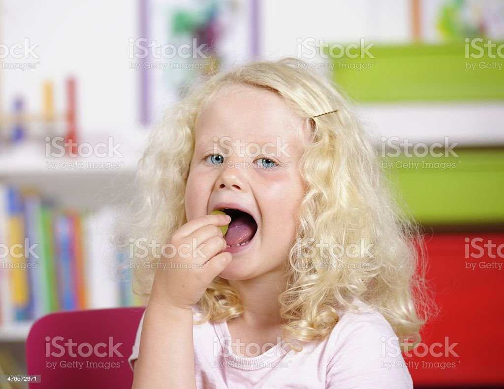 Blonde Little Girl Popping A Grape Into Her Mouth royalty-free stock photo