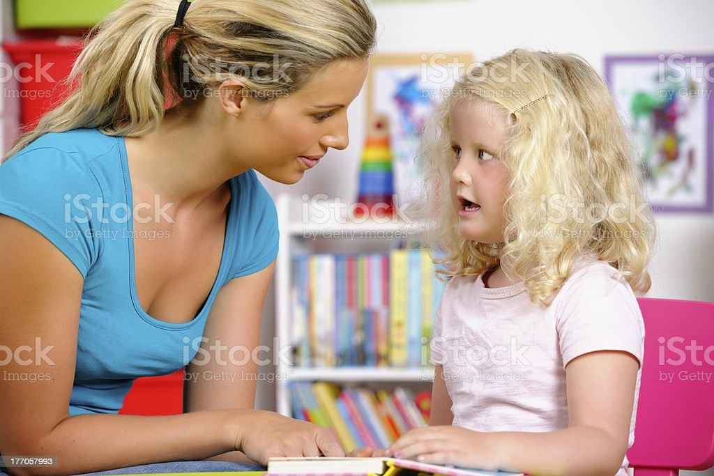 Blonde Little Girl Reading With Her Carer At Nursery royalty-free stock photo