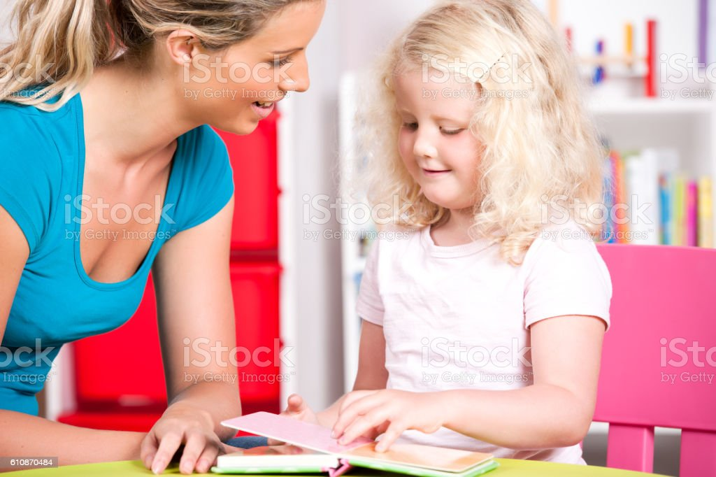 Blonde Little Girl Reading With Her Carer At Nursery stock photo