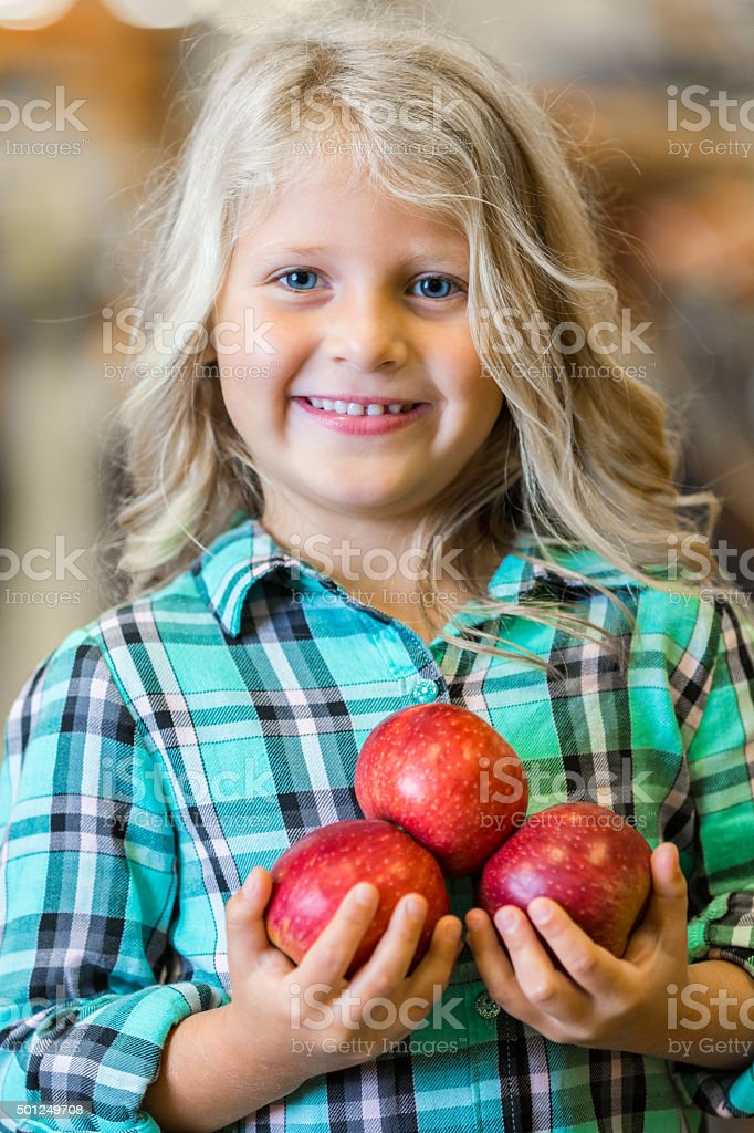 Blonde little girl smiling while holding apples in grocery store stock photo