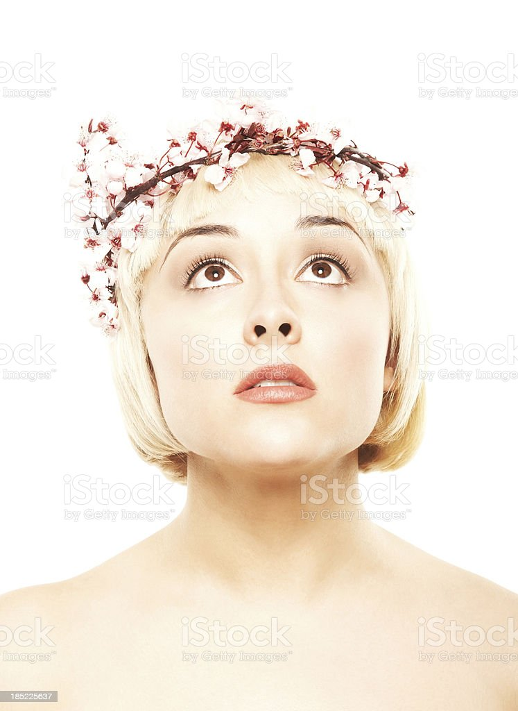 Blonde looking up with pink flowers on her head stock photo