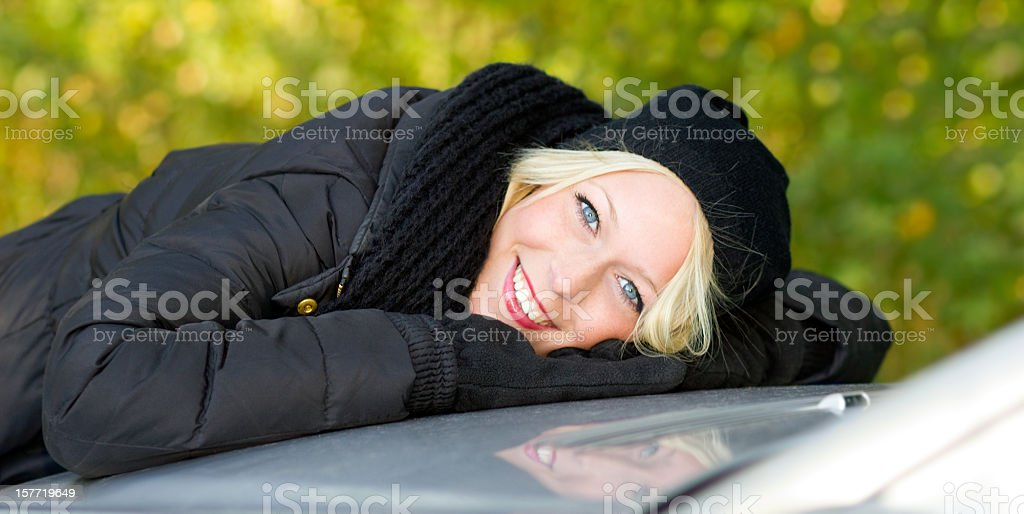 Blonde lying on the car hood smiling at camera stock photo