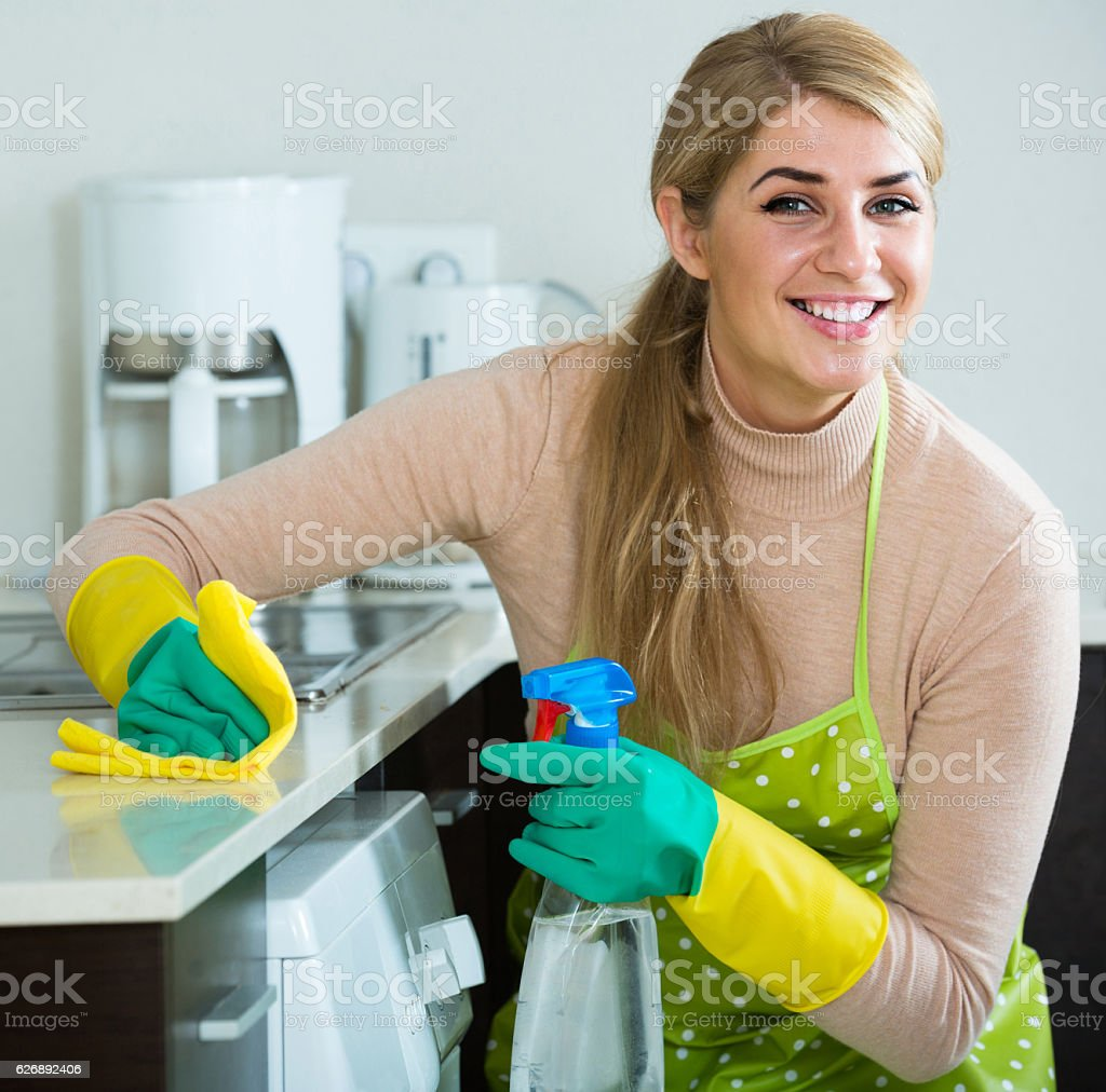 Blonde maid cleaning in domestic kitchen stock photo