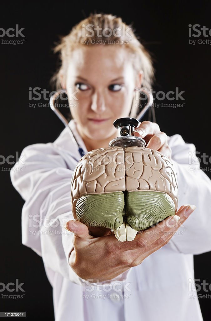 Blonde medical professional examining model brain with stethoscope looks sideways stock photo