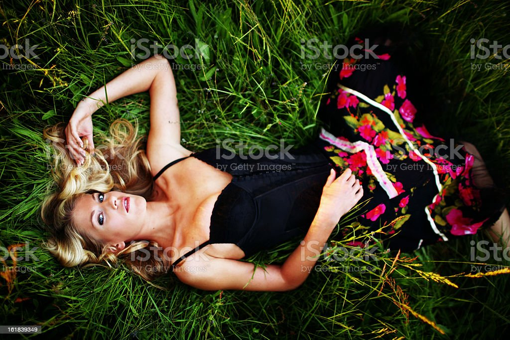 Blonde Model Lying in Grass with Black and Flowered Dress royalty-free stock photo