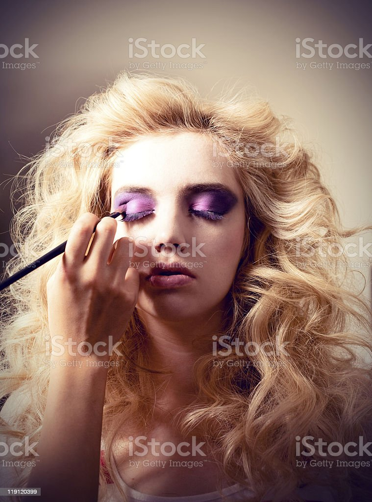 Blonde model putting on makeup for photo shoot royalty-free stock photo