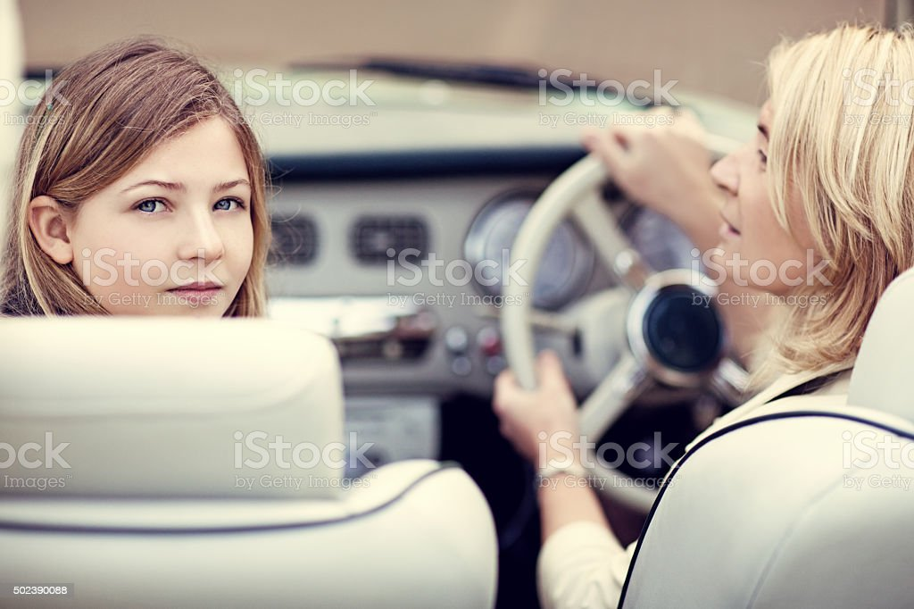 Blonde mother and daughter sitting in a vintage car stock photo