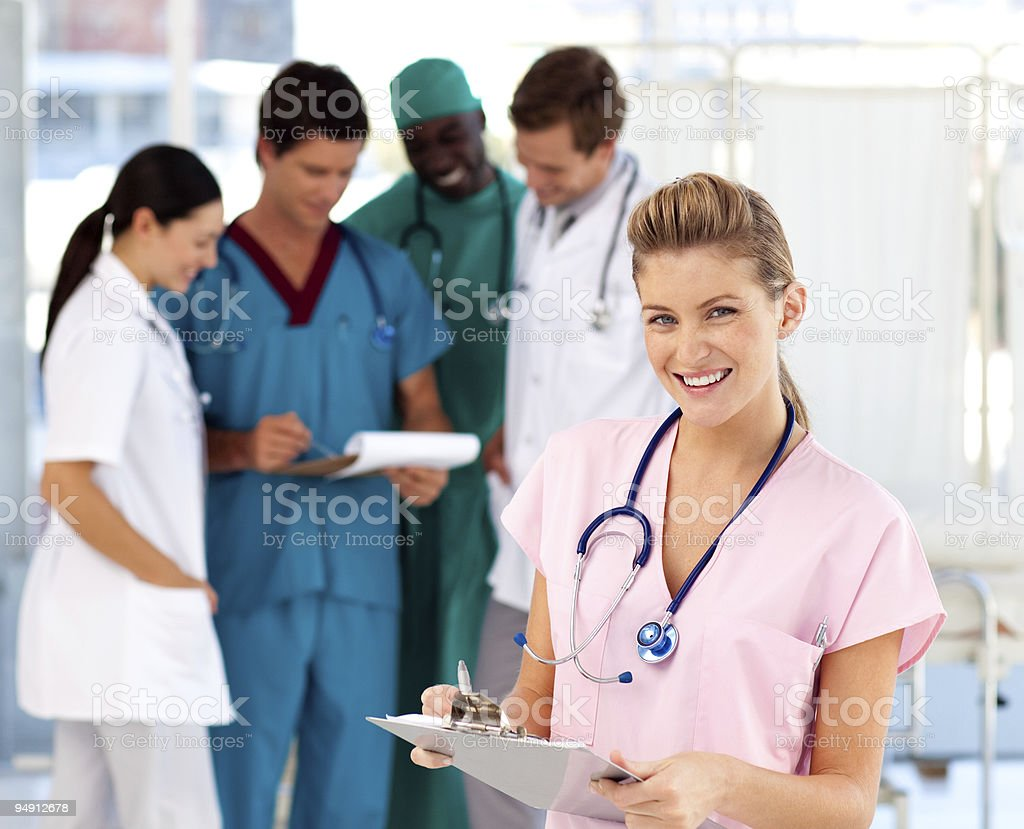 Blonde nurse with her team in the background royalty-free stock photo
