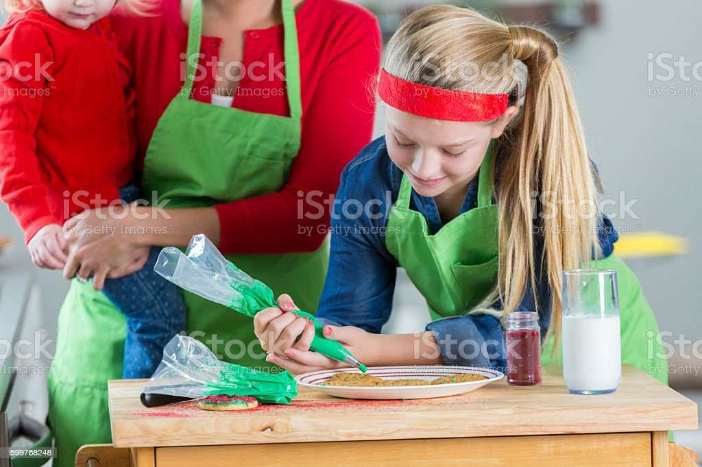 Blonde preteen decorating Christmas cookies stock photo