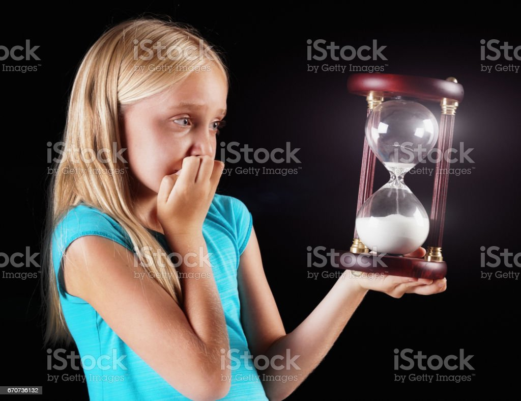 Blonde pre-teen girl looks at hourglass, biting her nails anxiously stock photo