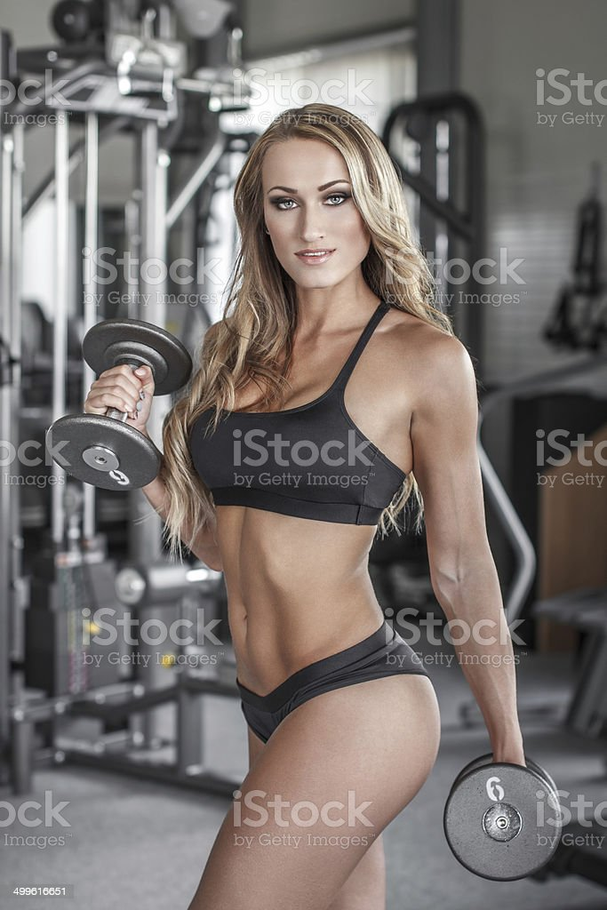 Blonde sexy bodybuilder workout with dumbbells royalty-free stock photo