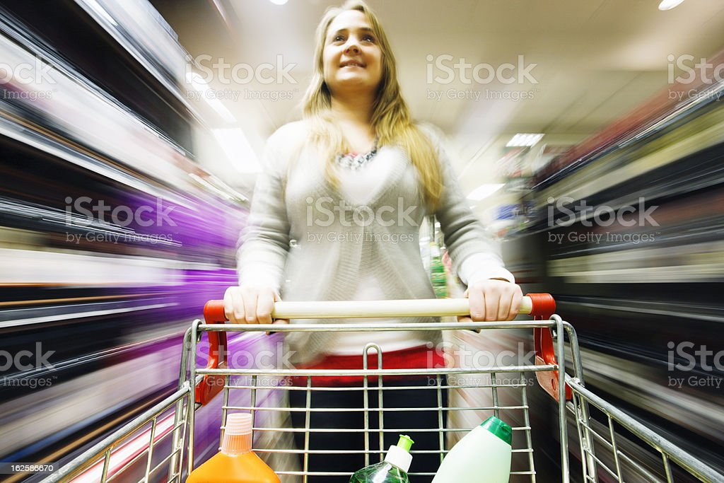 Blonde shopper racing through supermarket with multicolored motion blur royalty-free stock photo