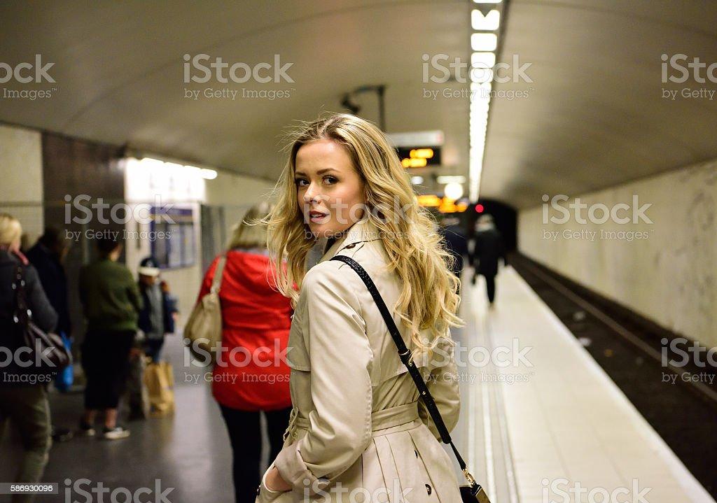 Blonde Swedish woman walking along commuter subway train platform stock photo
