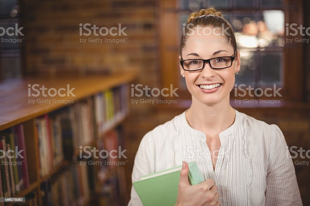 Blonde teacher holding book in the library stock photo