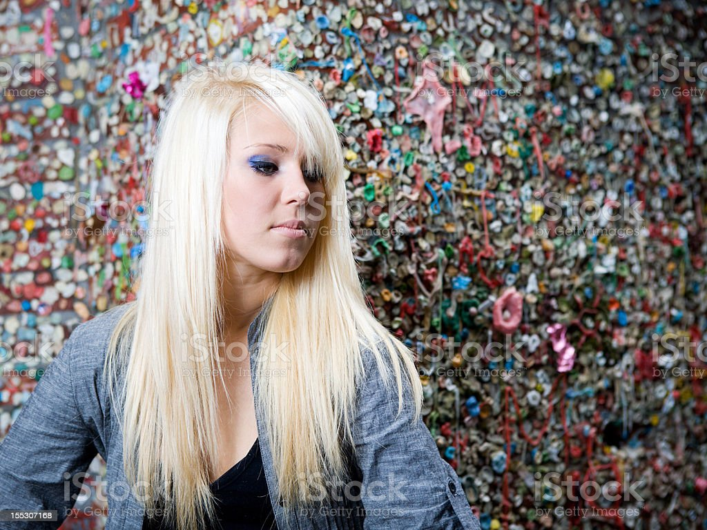 Blonde, teenage girl by gum wall stock photo