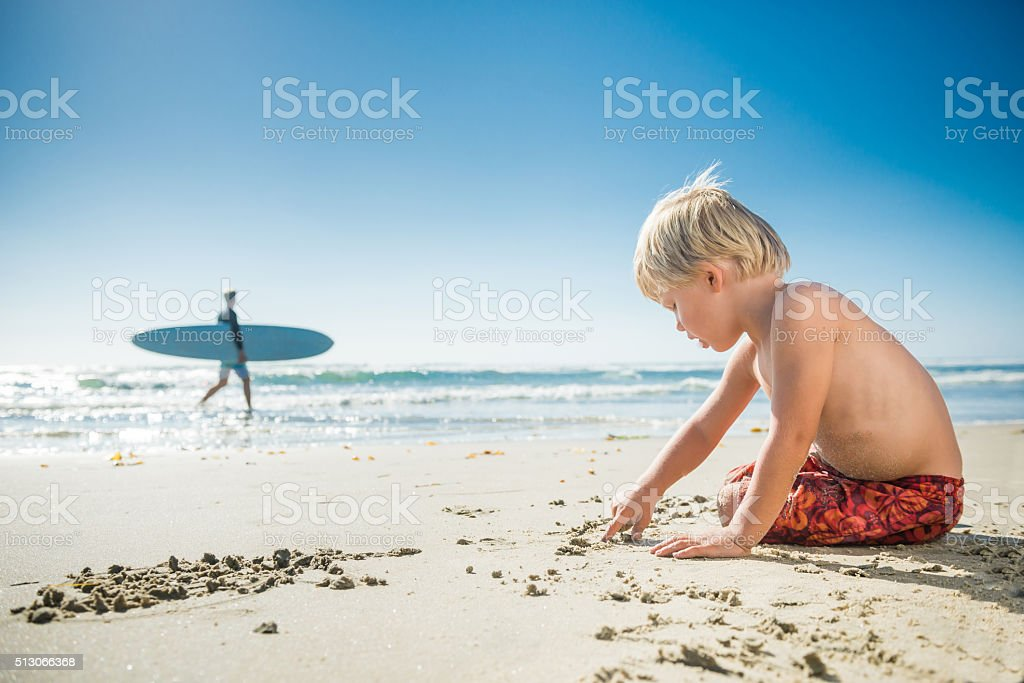 Blonde Three Year Old Boy Lying On The Beach stock photo