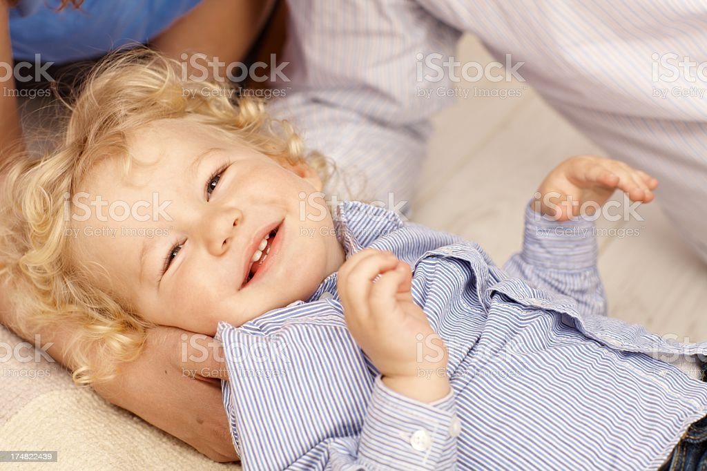 Blonde toddler boy lying in parents hand royalty-free stock photo