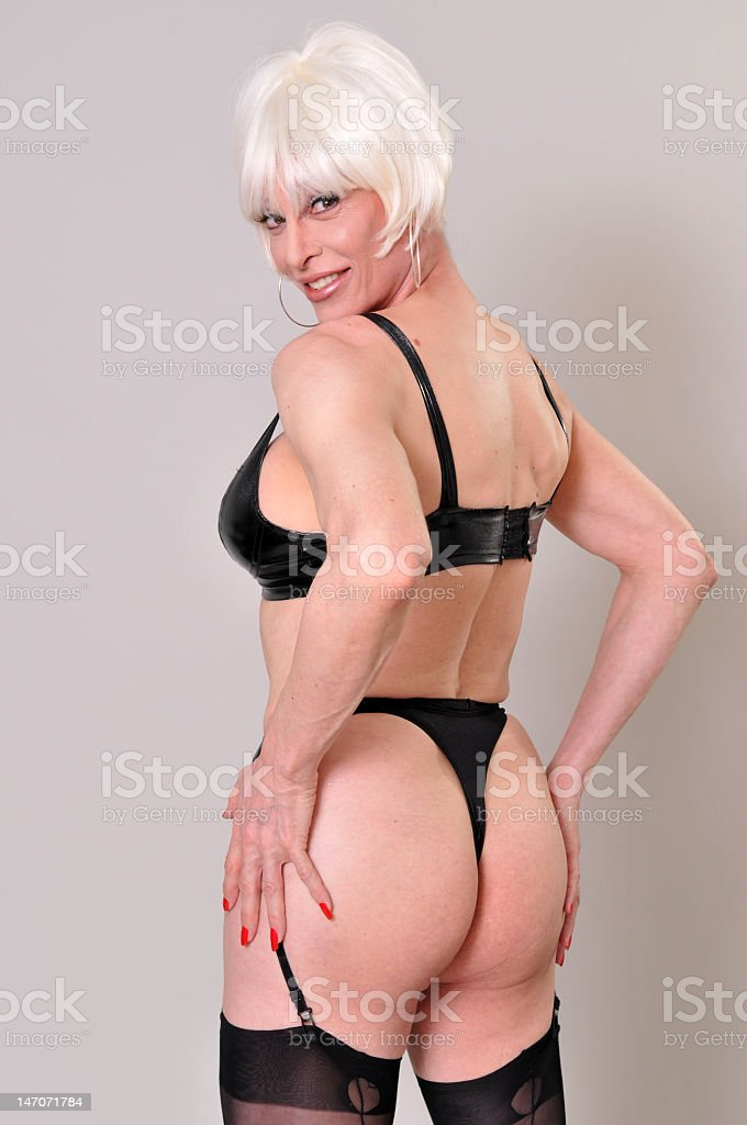 Blonde Transsexual wearing PVC boots and bra holding buttocks royalty-free stock photo